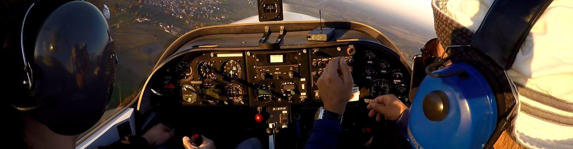 Zwei Piloten im Cockpit, ein Flugschüler bekommt von einem Fluglehrer etwas erklärt.