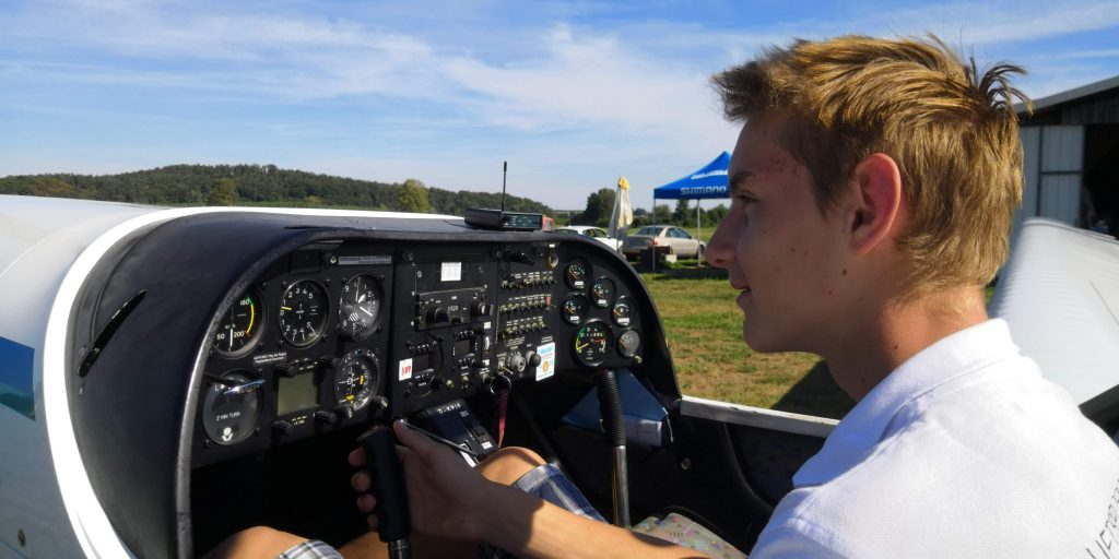 Ein junger Flugschüler bei der Vorflugkontrolle im Cockpit