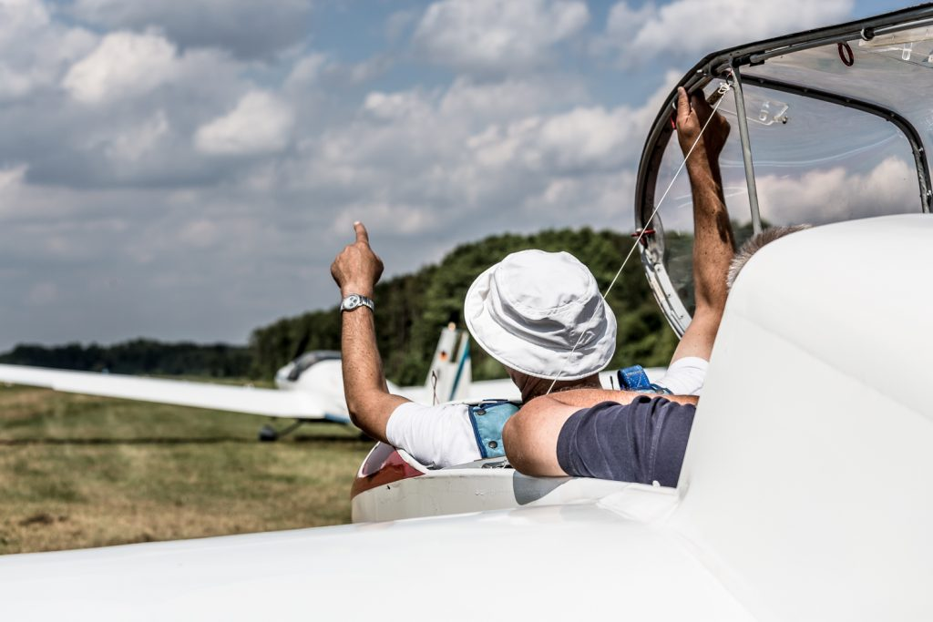 Ein Flugschüler deutet in die Richtung, in die der Start in dem Segelflugzeug gleich erfolgen wird.
